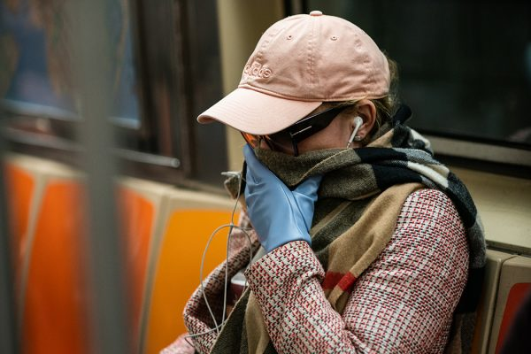 A woman wearing a protective mask sits in a subway car at Grand Central Terminal on March 12, 2020 in New York City.