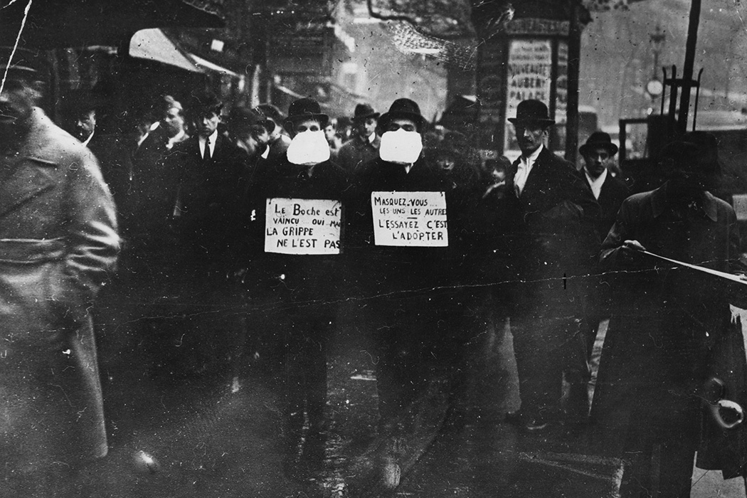 Two men wearing and advocating the use of flu masks in Paris during the Spanish flu epidemic, 1919