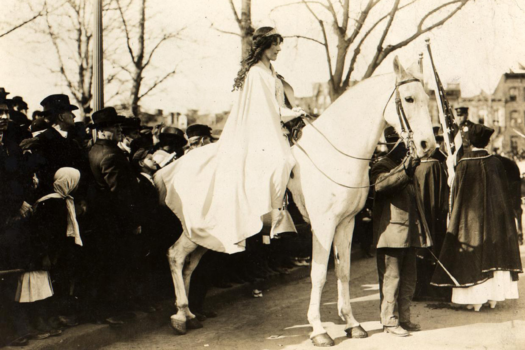 Lawyer Inez Milholland, wearing white cape, seated on white horse at the National American Woman Suffrage Association parade, March 3, 1913, Washington, D.C.