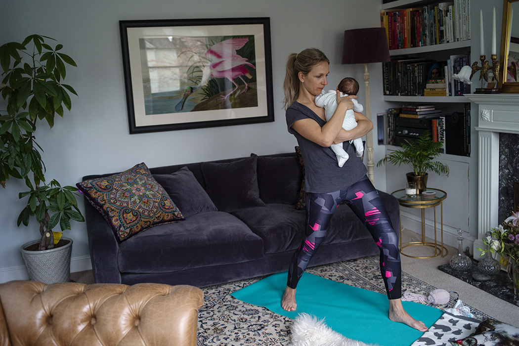 A mother and her baby doing yoga in their apartment