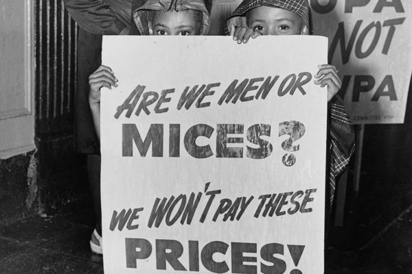 "Two young children holding placard which reads ""Are we men or mices? We won't pay these prices"" at a demonstration in Harlem between the 116th and the 125th to protest against housing conditions and rent price, New York City, US, July 1946."