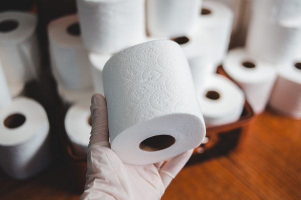 A gloved hand holding a roll of toilet paper