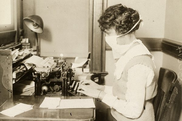 A typist wearing an influenza mask in 1918