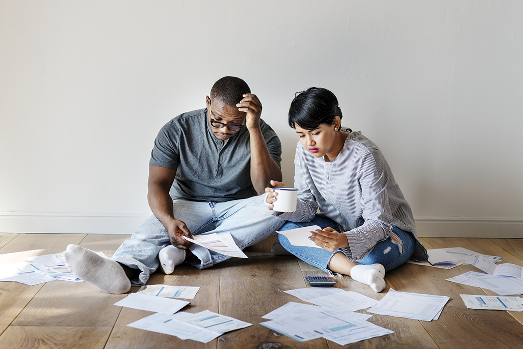 A couple sitting on the floor attempting to understand paperwork