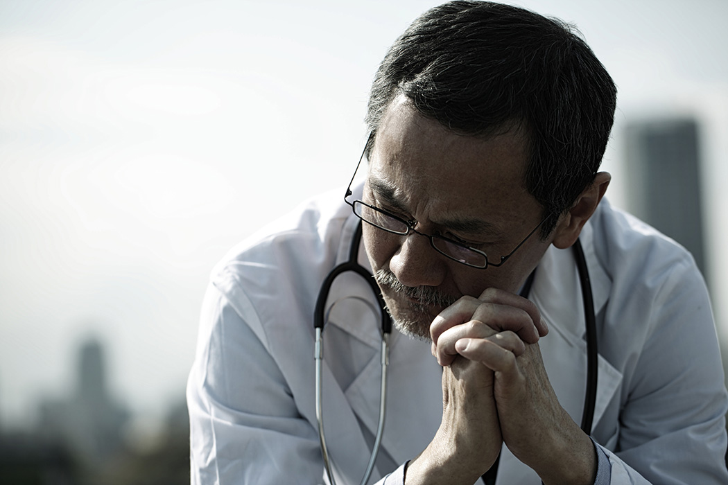 A male doctor sitting down and looking pensive