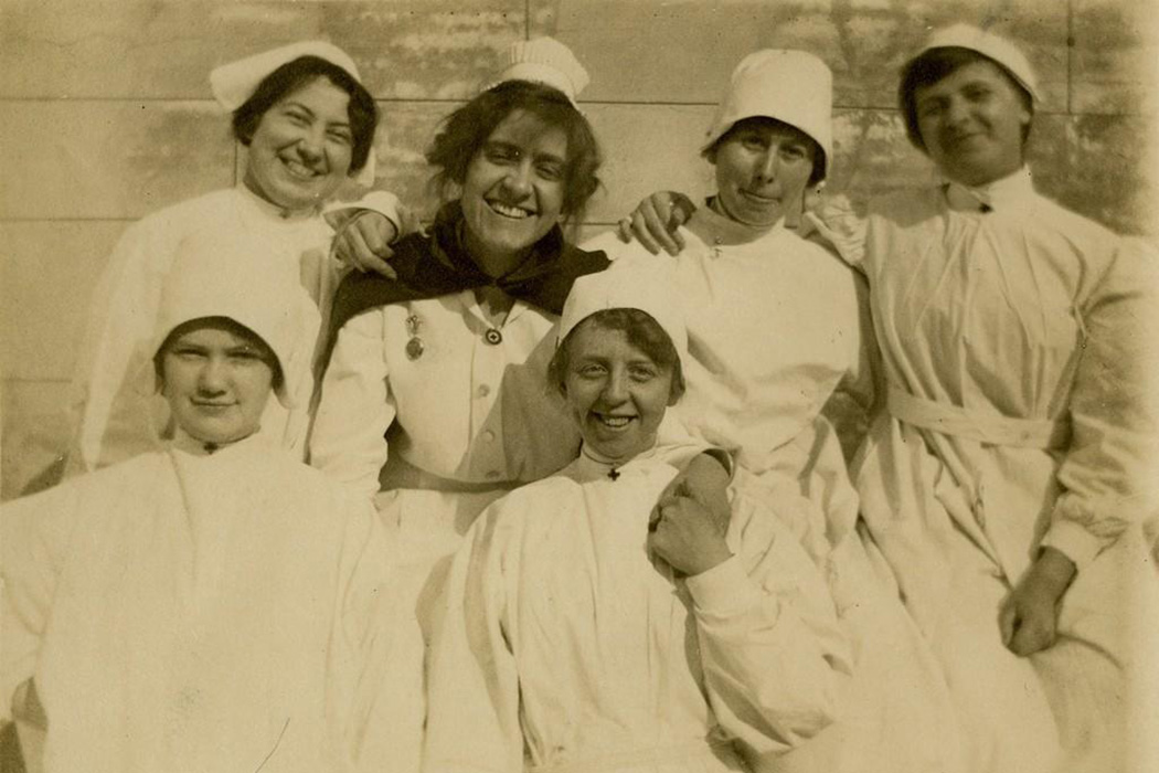 A graduate nurse and student nurses in isolation uniforms, early 1900s