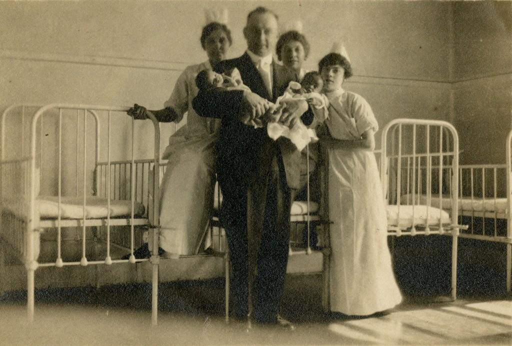 Three student nurse pose with a physician holding two infants, prior to 1904