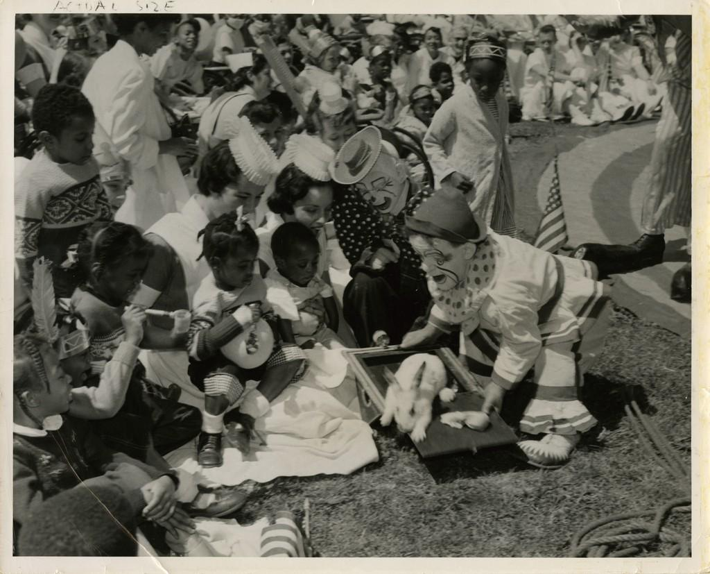 Two nurses sit with children in front of a pair of clowns during Circus Day, c. 1954