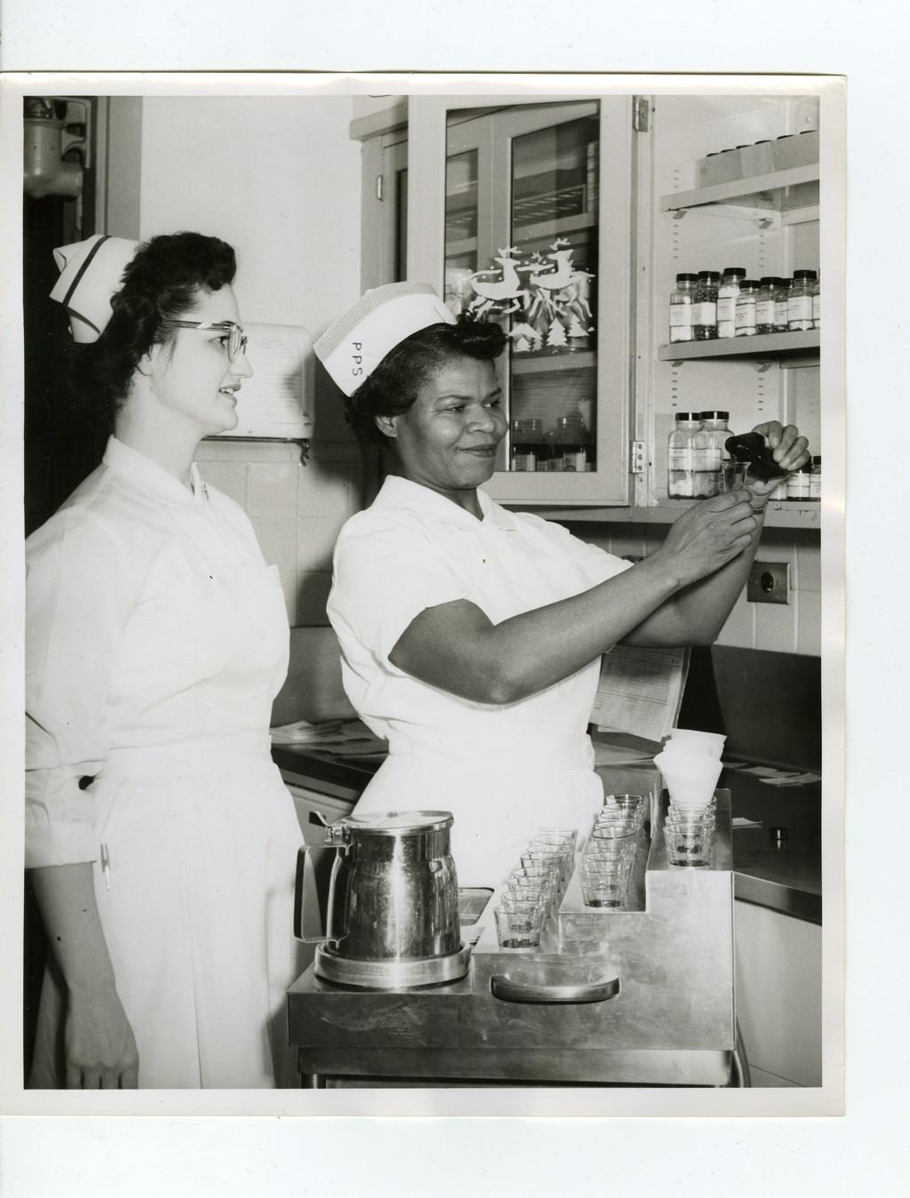 An instructor shows a practical nurse student how to pour medication, c. 1958