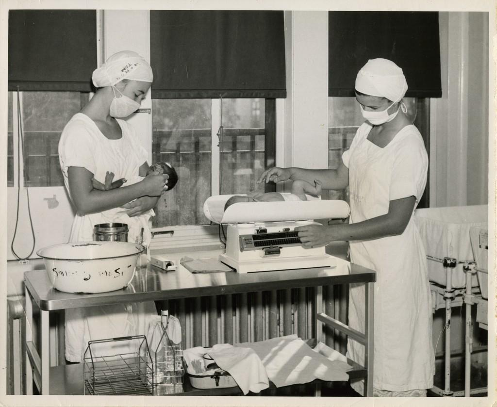 Two nurses weigh babies in the Nursery, c. 1954