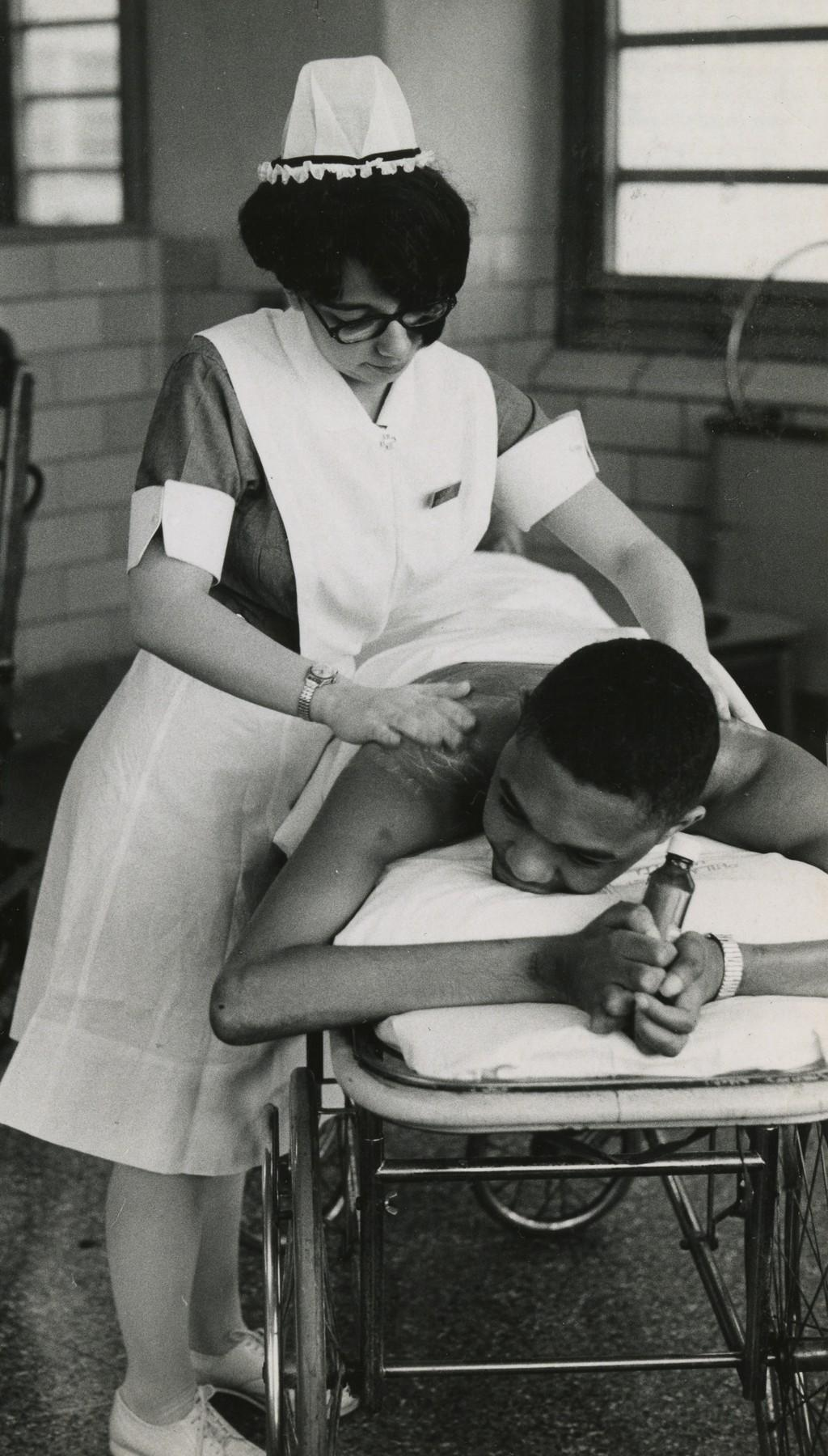 A student nurse tends to a patient, c. 1954