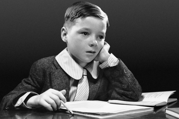 Boy sitting at desk with book