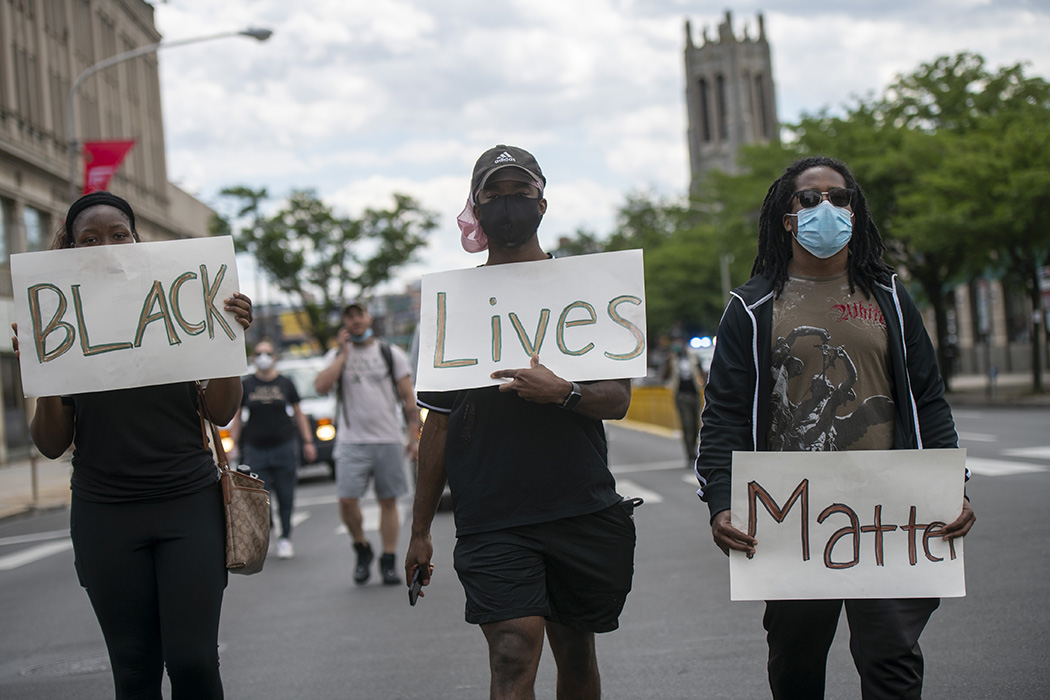 "Protesters march with three placards stating ""BLACK Lives Matter"" in the aftermath of widespread unrest following the death of George Floyd on June 1, 2020 in Philadelphia, Pennsylvania."