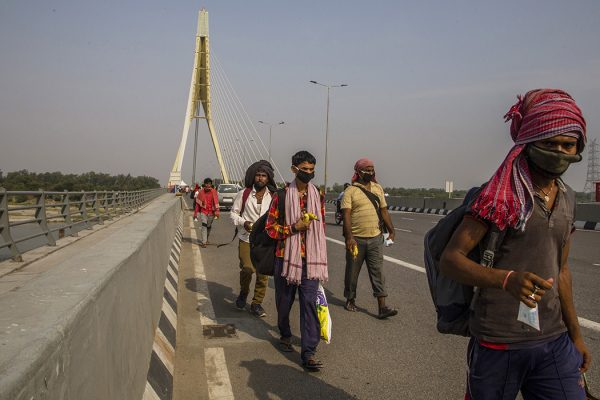 Indian migrant workers walk on a bridge after they were stopped by police while returning to their native places, as the country relaxed its lockdown restriction on May 14, 2020 in New Delhi, India