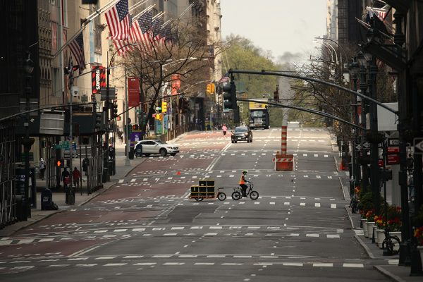 A delivery person is seen crossing a nearly empty 5th Avenue during the coronavirus pandemic on April 25, 2020 in New York City