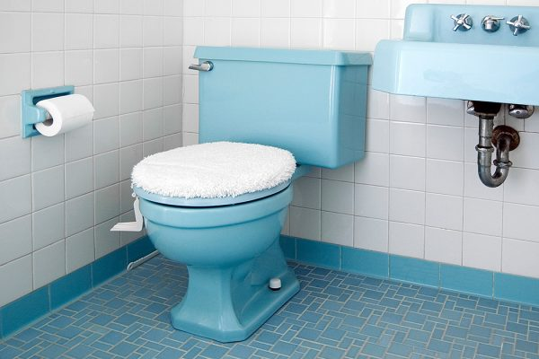 A blue toilet with its lid closed