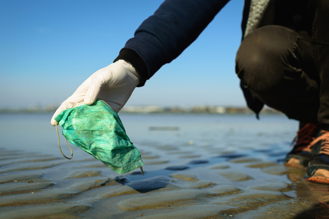Man holding Dirty used disposable medical mask on beach by sea. Pollution due coronavirus pandemic