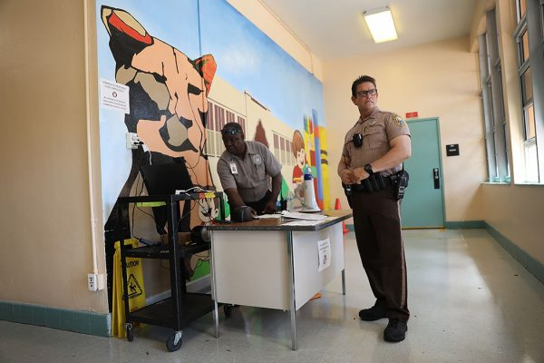 The head of school security, and a Miami-Dade Police officer stand at the front entrance to the Kenwood K-8 Center on August 24, 2018 in Miami, Florida.
