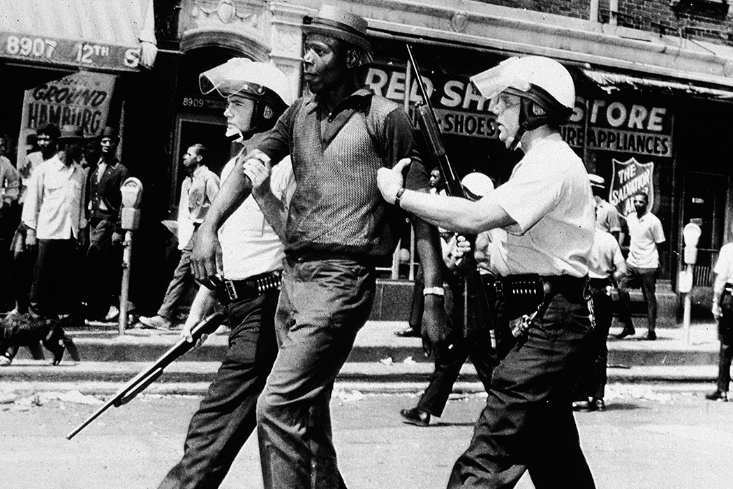Two police officers in full riot gear arrest a Black man during a breakout of rioting and looting on the West side of Detroit, Michigan, July 23, 1967.