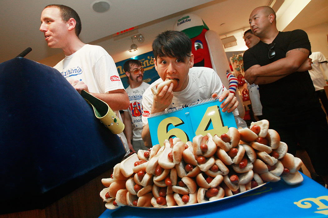 Former champion Takeru Kobayashi bites a hot dog as reigning champion Joey Chestnut (L) speaks at the Nathan's Famous Fourth of July International Hot Dog Eating Contest official weigh-in ceremony July 2, 2009 in New York City