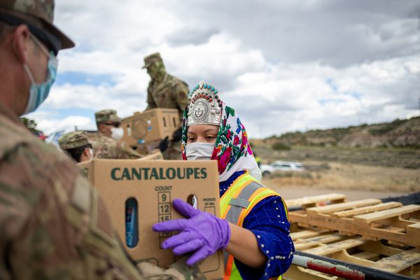 Miss Navajo Nation Shaandiin P. Parrish grabs a box filled with food and other supplies to distribute to Navajo families on May 27, 2020 in Counselor on the Navajo Nation Reservation, New Mexico.