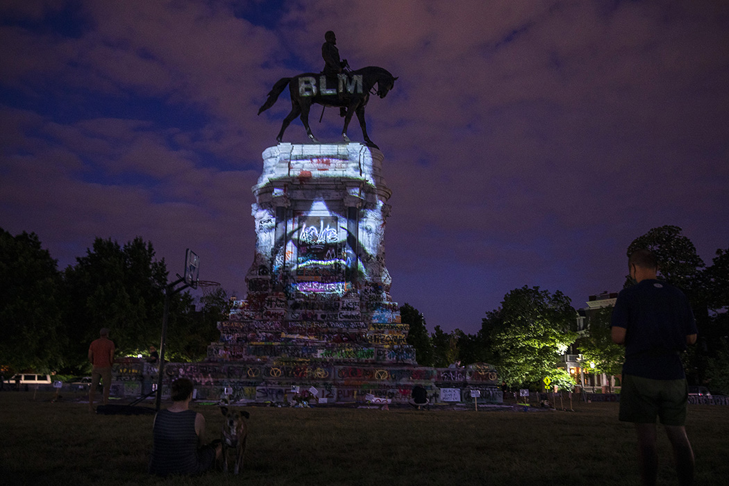 George Floyd's image is projected on the Robert E. Lee Monument as people gather around on June 18, 2020 in Richmond, Virginia.