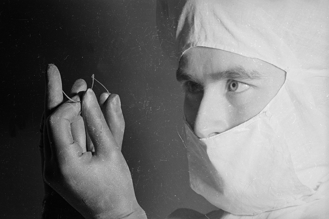 A man wearing a surgical mask and gloves threading his needle with suture before an operation.