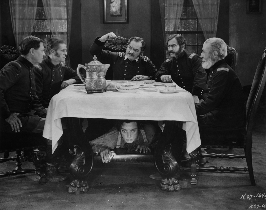 Buster Keaton hiding under table as group of men plan in a scene from the film 'The General', 1926