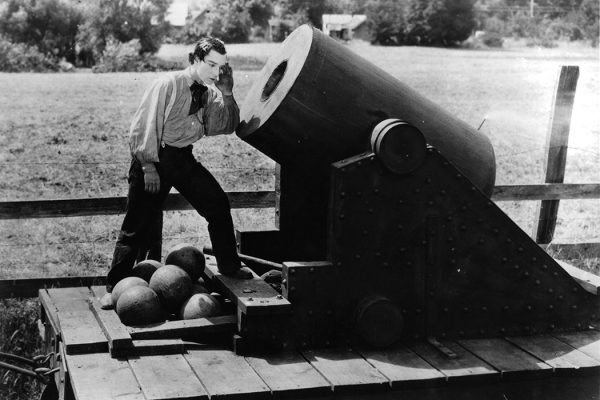 Buster Keaton putting his ear to cannon in a scene from the film 'The General', 1926