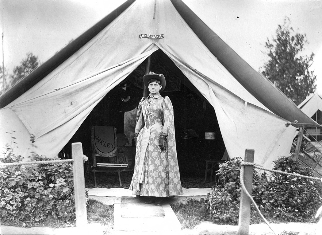 Annie Oakley in front of her tent, 1889