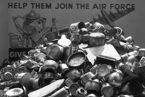 A pile of pots, pans, and kitchen utensils sits in front of a poster urging people to donate aluminum kitchen ware to help the US Air Force