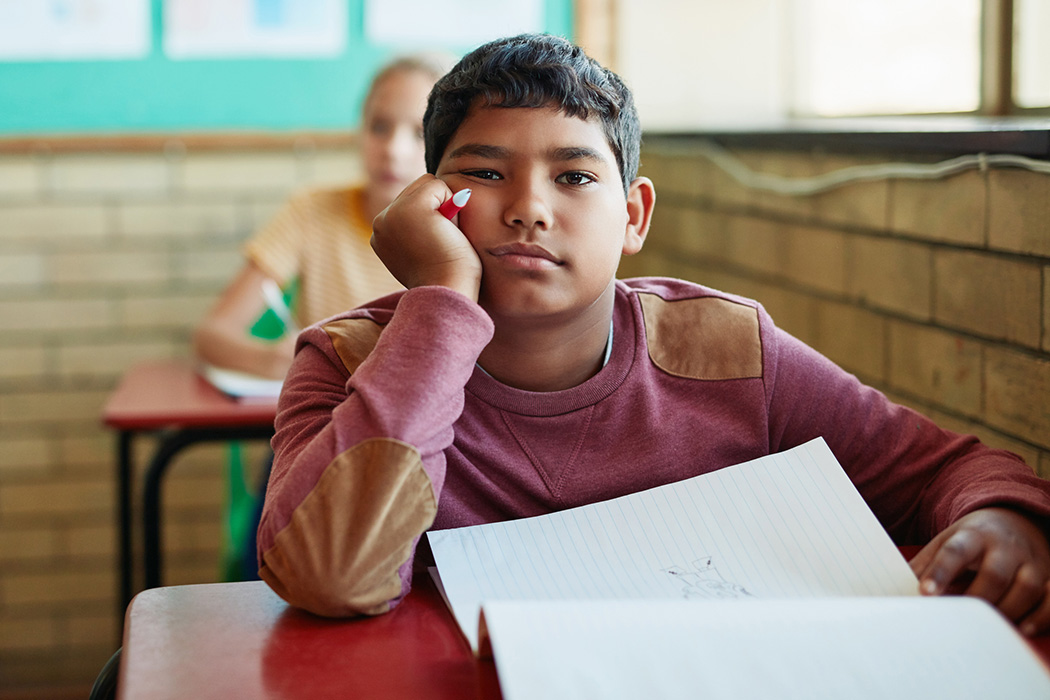 A young boy looking bored at his desk in a classroom