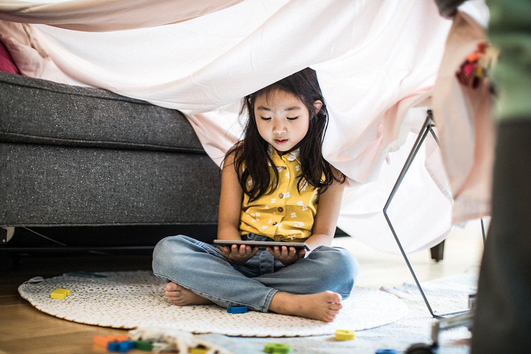 Young girl using tablet in homemade fort at home
