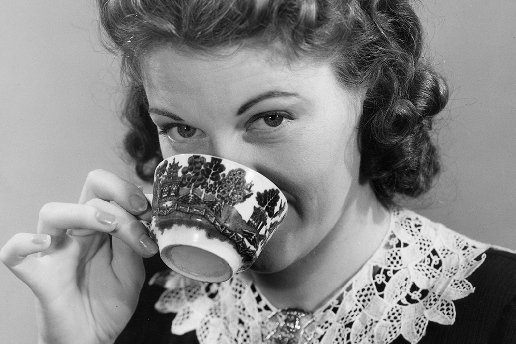 :A woman drinking from a cup of tea