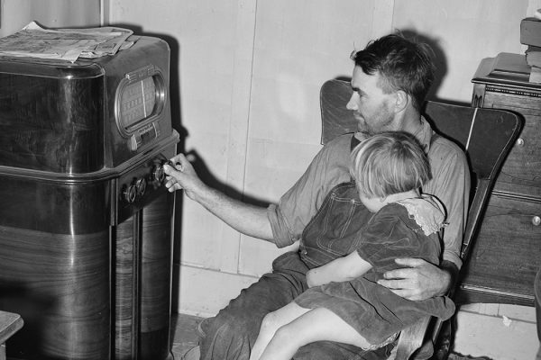 John Frost and daughter listening to radio in their home. Tehama County, California
