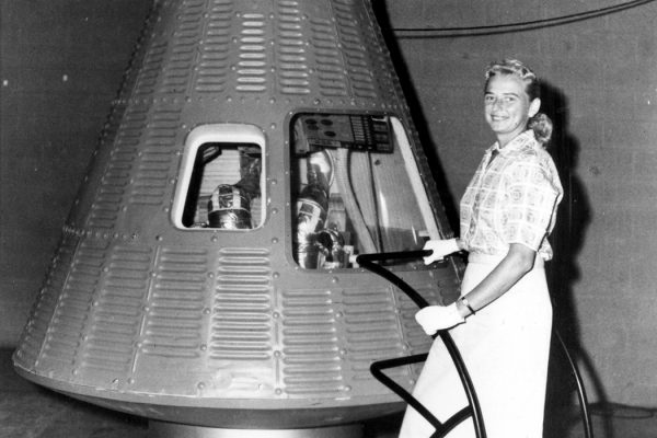 Jerrie Cobb poses next to a Mercury spaceship capsule.