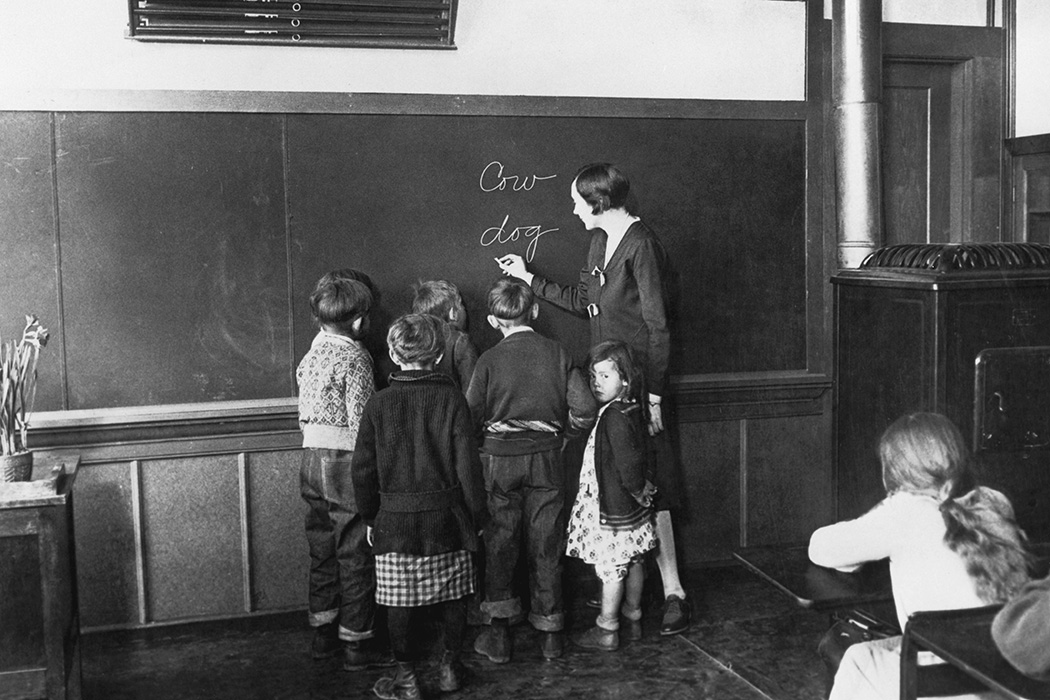 A teacher teaches her young pupils how to spell, 1930.