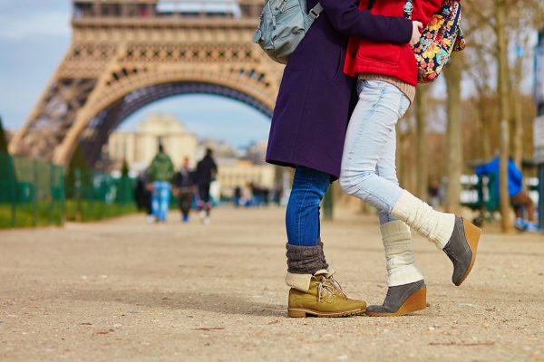 Two women hugging in front of the Eiffel Tower in Paris