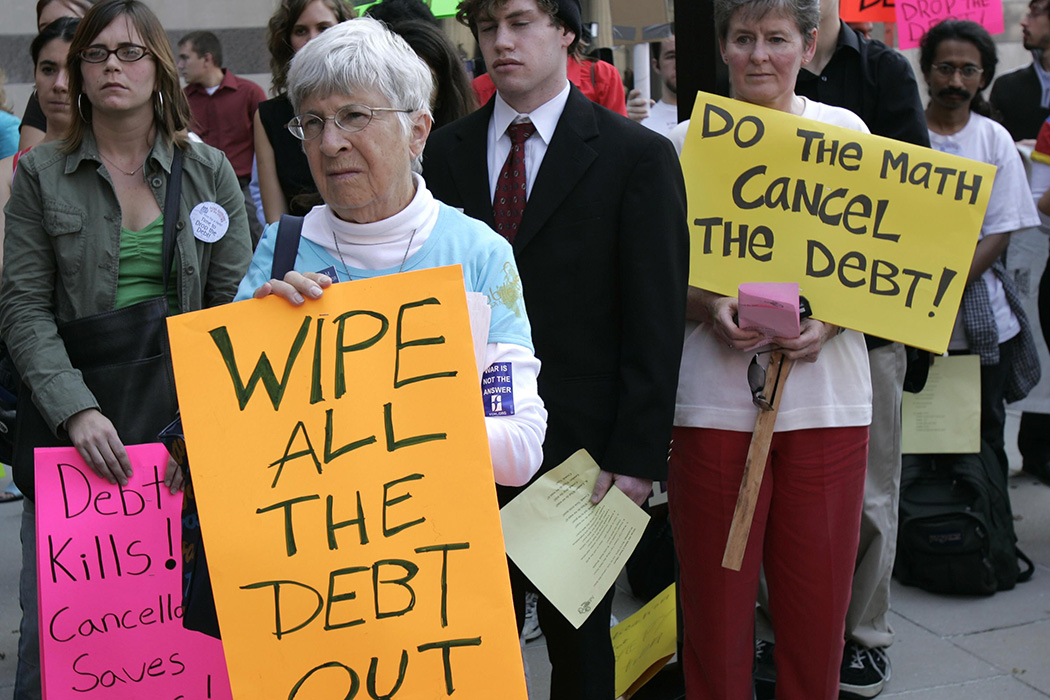Miriam Bauerlin holds a sign pleading for debt cancelation during a protest near the US Treasury Department October 1, 2004 in Washington, DC.