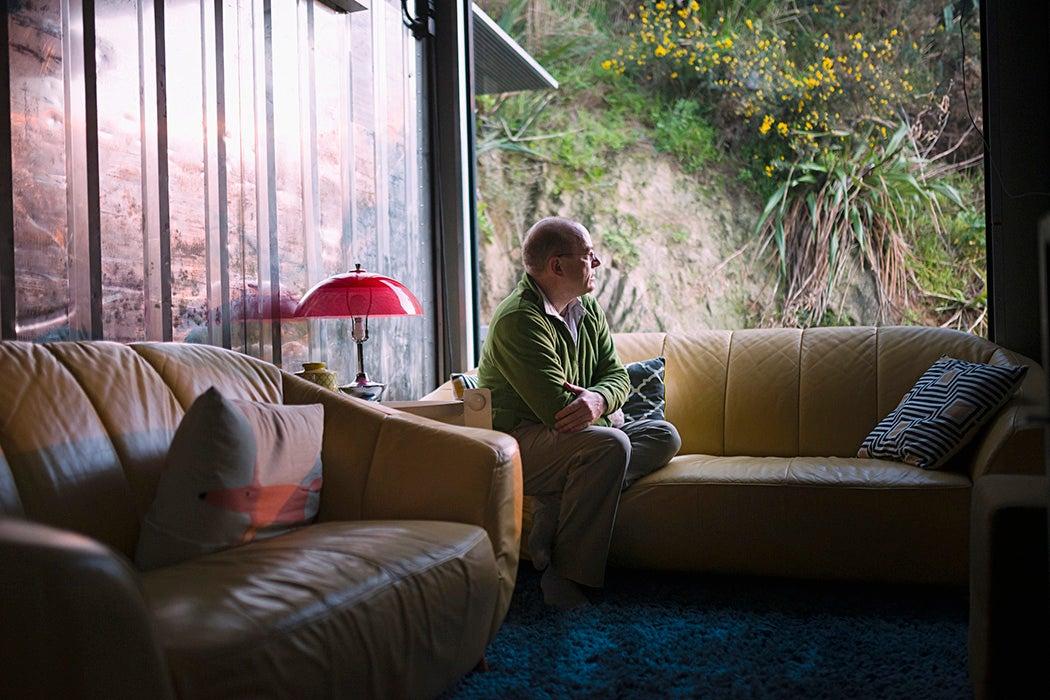 Pensive Caucasian man sitting on sofa near window