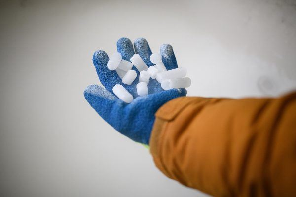 A hand holding coarse dry ice pellets