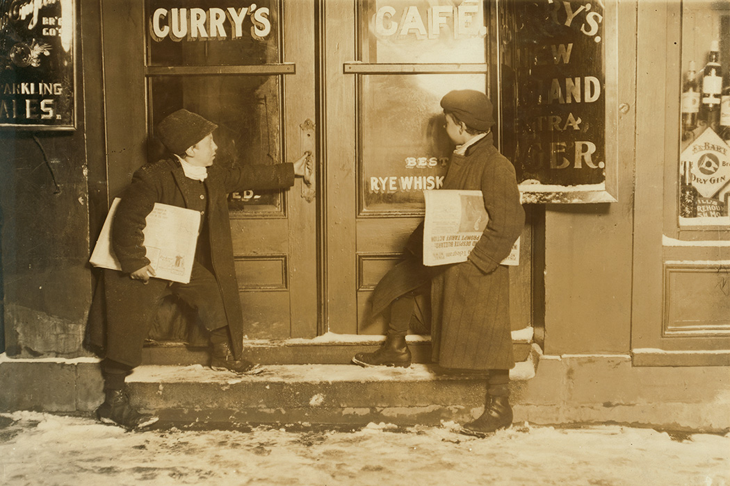 Two boys selling newspapers outside of a saloon