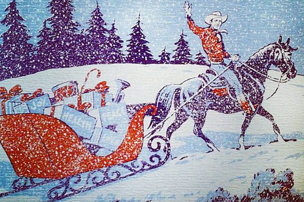 A cowboy pulling a sleigh of gifts