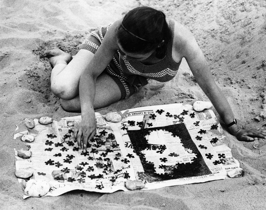 A girl solving a jigsaw puzzle on a beach, 1934
