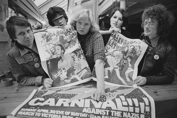 English designer and typographer Roger Huddle with collaborators holding posters for 'Rock against Racism' and 'RAR/Anti Nazi League Carnival', London, UK, 27th April 1978