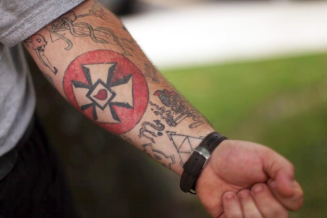 A man displays a Ku Klux Klan cross tattooed onto his arm