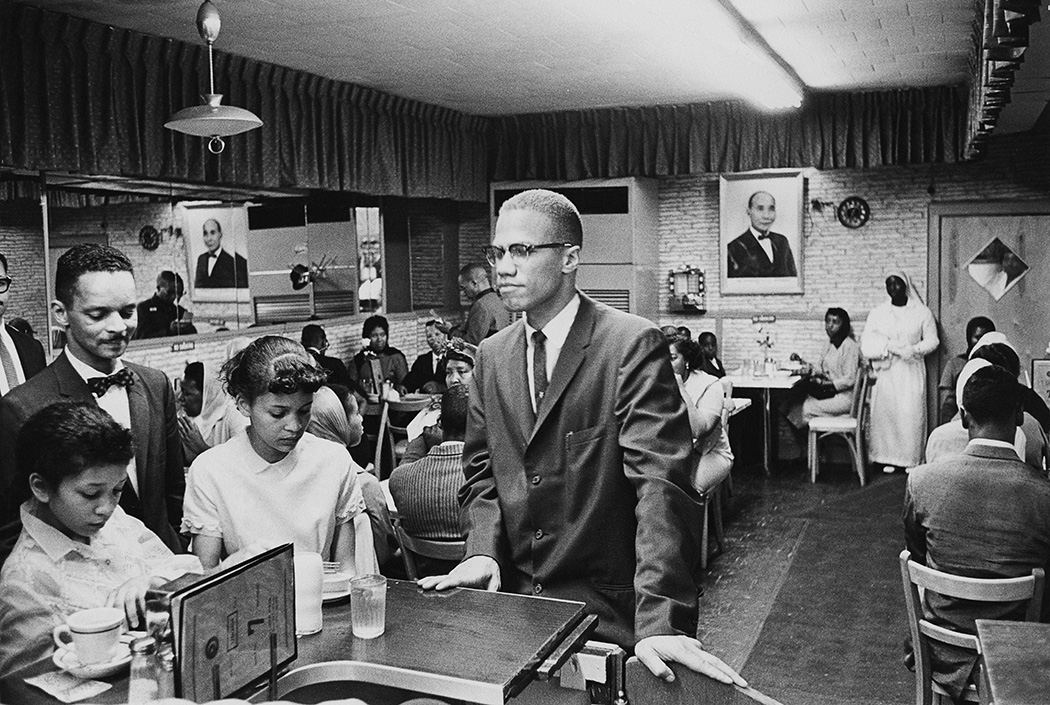 Malcolm X at Temple 7, a Halal restaurant on Lenox Avenue and 116th Street, Harlem, 1963
