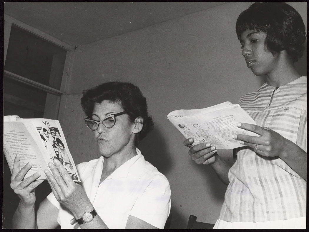 Two women read together at a literacy center near Havana