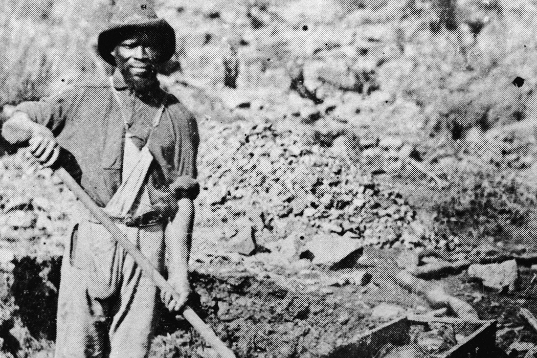 An African-American miner poses with a shovel in Auburn Ravine during the Gold Rush, California, 1852.