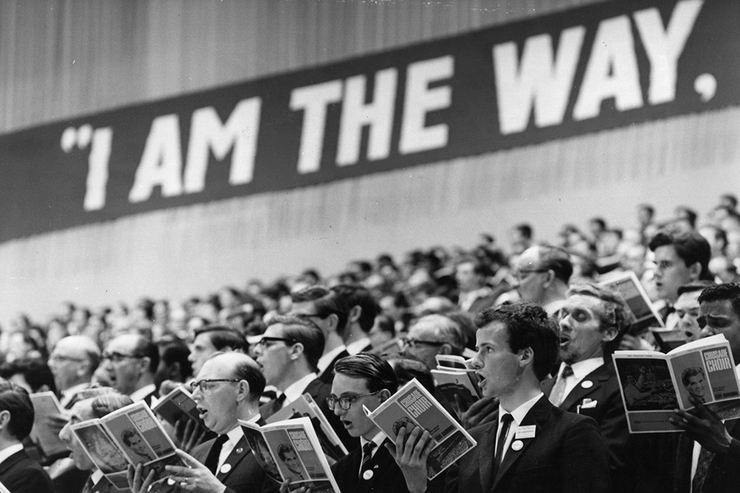 Photograph: A choir at the  Billy Graham evangelist crusade at London's Earls Court sing to 20,000 crowd under the  slogan ' I am the way'.    Source: Photo by Fox Photos/Getty Images